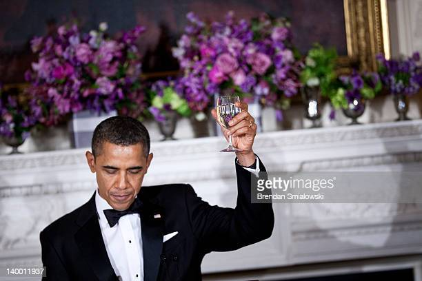 US President Barack Obama makes a toast after speaking in the State Dining Room of the White House February 26 2012 in Washington DC President Obama...