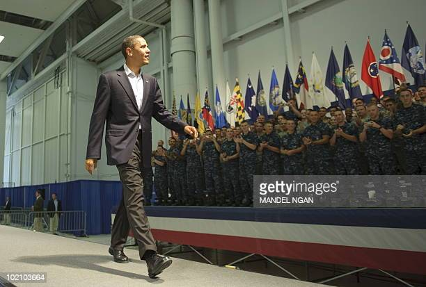 US President Barack Obama makes his way onto the stage to speak to military personnel at the Naval Air Technical Training Center of the Pensacola...