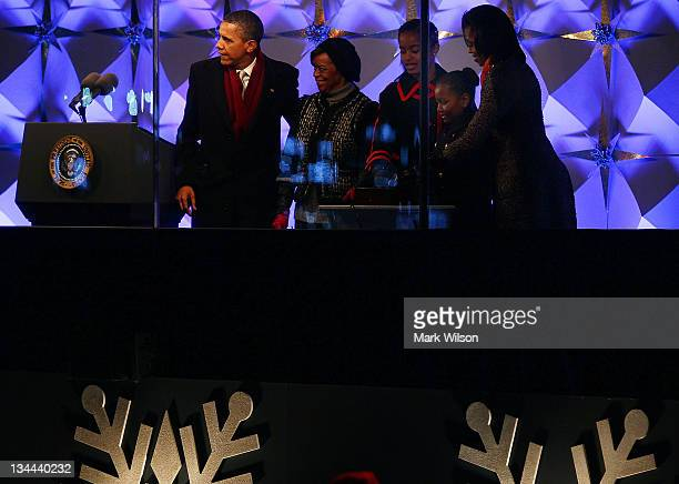 President Barack Obama Marion Robinson first lady Michelle Obama and daughters Sasha and Malia help light the National Christmas Tree on December 1...