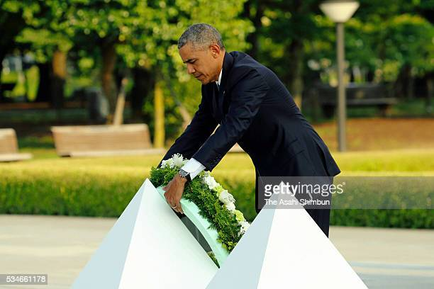 US President Barack Obama offers a wreath at the cenotaph at the Hiroshima Peace Memorial Park on May 27 2016 in Hiroshima Japan Obama becomes the...