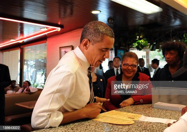 US President Barack Obama orders for food at the Roscoe's Chicken and Waffles in Los Angeles California on October 24 2011 Obama said the vast...