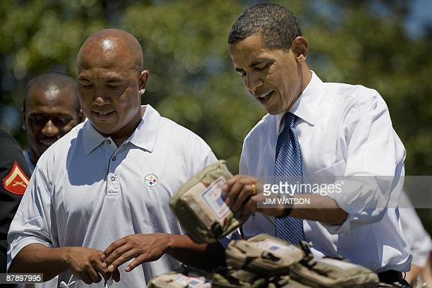US President Barack Obama packs USO care packages with Pittsburg Steelers Wide receiver Hines Ward during a service event on the South Lawn of the...