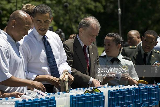 US President Barack Obama packs USO care packages with Pittsburg Steelers Wide Receiver Hines Ward and US Senator Arlen Specter during a service...