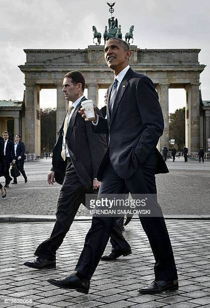 President Barack Obama passes the Brandenburg Gate while walking from the US Embassy to the Adlon Hotel November 17, 2016 in Berlin, Germany. US...