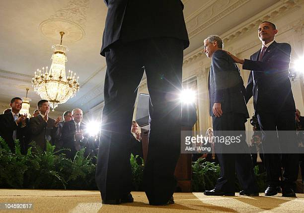 President Barack Obama pats on the back of chief of staff Rahm Emanuel during Emanuel's resignation announcement in the East Room October 1, 2010 at...