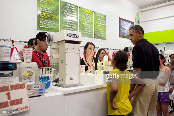 US President Barack Obama pauses while his younger daughter Sasha decides on Shave Ice flavors at Island Snow at Kailua Beach Center on December 27...