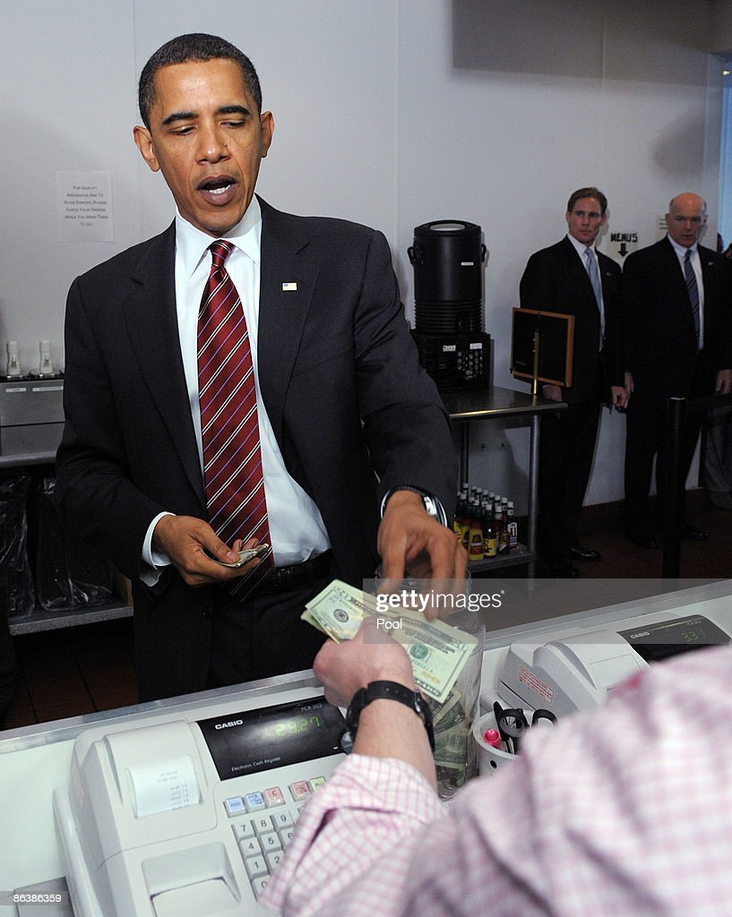U.S. President Barack Obama pays after ordering lunch at Ray's Hell Burger May 5, 2009 in Arlington, Virginia. Obama and Biden made an unannouced vist to the Arlington restaurant.