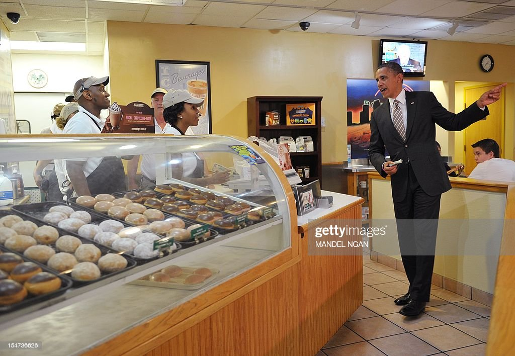 US President Barack Obama picks up an order of donuts at a Krispy Kreme donuts store in Tampa, Florida, on October 25, 2012. Obama pursued the sunset west then turned around and chased the dawn, streaking across America on an eight-state marathon as his re-election bid hit top gear. AFP PHOTO / Mandel NGAN