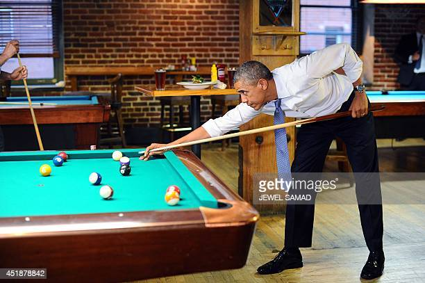 US President Barack Obama plays a game of pool with Colorado Governor John Hickenlooper at a pub in Denver Colorado on July 8 2014 AFP PHOTO/Jewel...