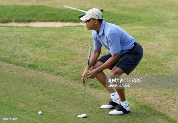 US President Barack Obama plays golf at MidPacific Country Club in Kailua Hawaii on December 23 2013 The first family is in Hawaii for their annual...