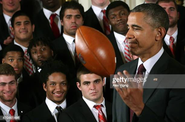S President Barack Obama plays with a football as members of the Ohio State University Buckyes football team look on during an East Room event at the...