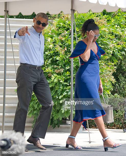 US President Barack Obama points towards the assembled press as he and first lady Michelle Obama depart the White House August 6 2016 in Washington...