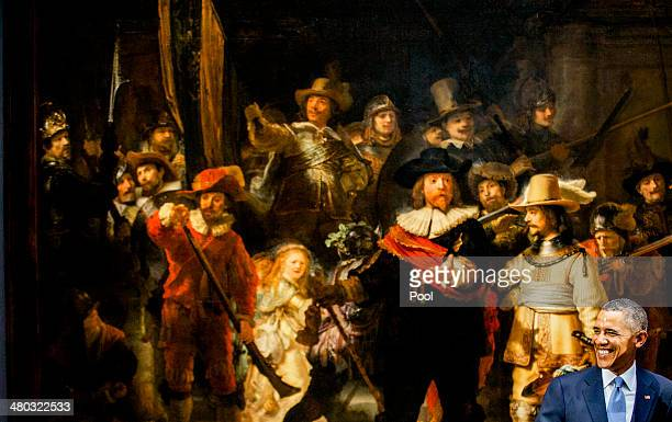 President Barack Obama poses for photographs during a press conference in front of Rembrandt's 'The Night Watch' on a visit to the Rijksmuseum ahead...