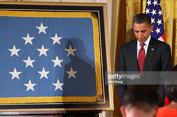 S President Barack Obama prays during an East Room presentation ceremony of a Medal of Honor October 6 2010 at the White House in Washington DC Army...