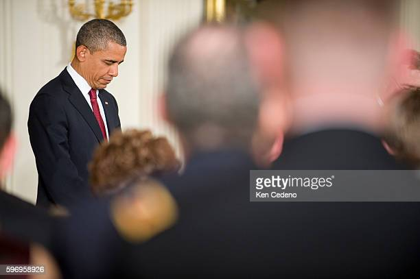 US President Barack Obama prays prior to awarding Specialist Leslie H Sabo Jr US Army the Medal of Honor for conspicuous gallantry to his widow Rose...