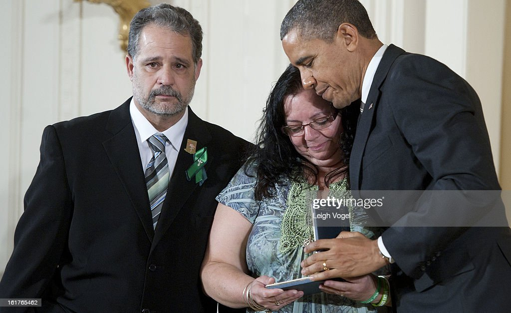 President Barack Obama presents Donna and Carlos Soto Sr. with the 2012 Presidential Citizens Medal on behalf of their daughter Victoria Soto at the White House on February 15, 2013 in Washington, DC.