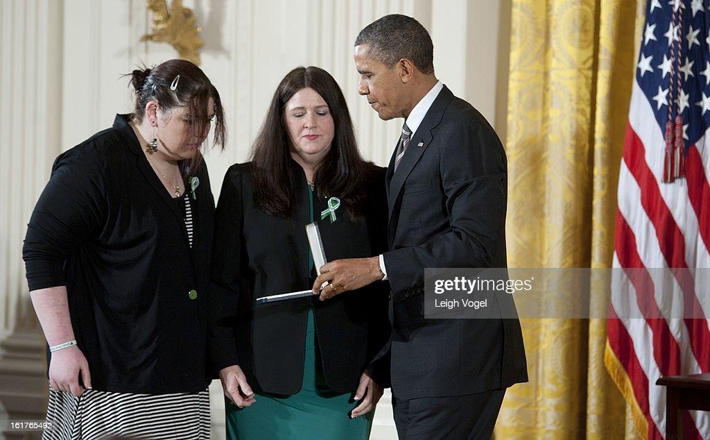 President Barack Obama presents Mary D'Avino and Sarah D'Avino the 2012 Presidential Citizens Medal on behalf of Rachel D'Avino for at the White House on February 15, 2013 in Washington, DC.