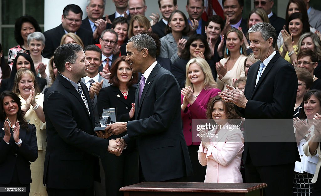 U.S. President Barack Obama (C) presents the 2013 National Teacher of the Year award to recipient Jeff Charbonneau (L), a high school science teacher from Zillah, Washington, as Secretary of Education Arne Duncan looks on during a Rose Garden event at the White House April 23, 2013 in Washington, DC. President Obama held the event to honor the 2013 National Teacher of the Year and finalists for their hard work and dedication in the classroom.