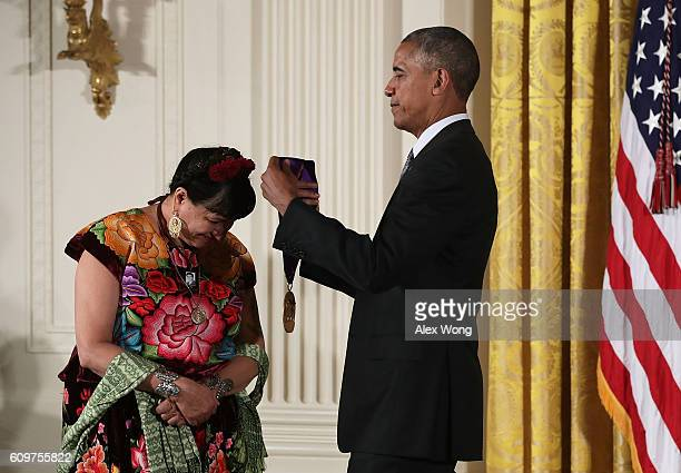 S President Barack Obama presents the National Medal of Arts to author Sandra Cisneros during an East Room ceremony at the White House September 22...