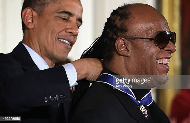 S President Barack Obama presents the Presidential Medal of Freedom to singer songwriter Stevie Wonder during an East Room ceremony at the White...
