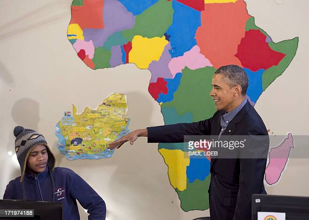 President Barack Obama pretends to drop a microphone alongside Aviwe Mtongana after Mtongana performed a rap during a tour of the Desmond Tutu HIV...