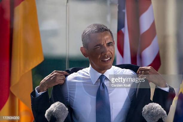 S President Barack Obama pulls the jacket from his shoulders while he speaks at the Brandenburg Gate on June 19 2013 in Berlin Germany Obama is...