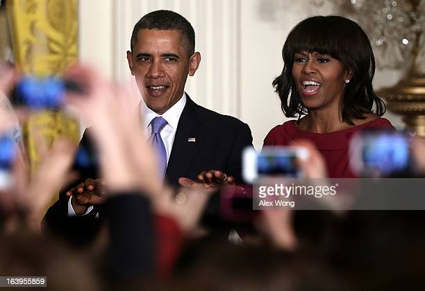 S President Barack Obama quiets the crowd as first lady Michelle Obama cheers during a Women's History Month Reception in the East Room of the White...