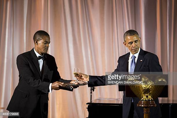 US President Barack Obama reaches for a glass to make a toast during a dinner for participants of the US Africa Leaders Summit August 5 2014 in...