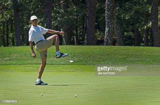 US President Barack Obama reacts to a missed putt on the first green at Farm Neck Golf Club in Oak Bluffs Massachusetts August 11 2013 during the...