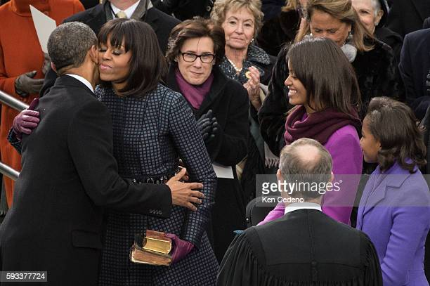 US President Barack Obama receives a hug and kiss from First Lady Michelle Obama after being sworn by The Honorable John Roberts Chief Justice of the...