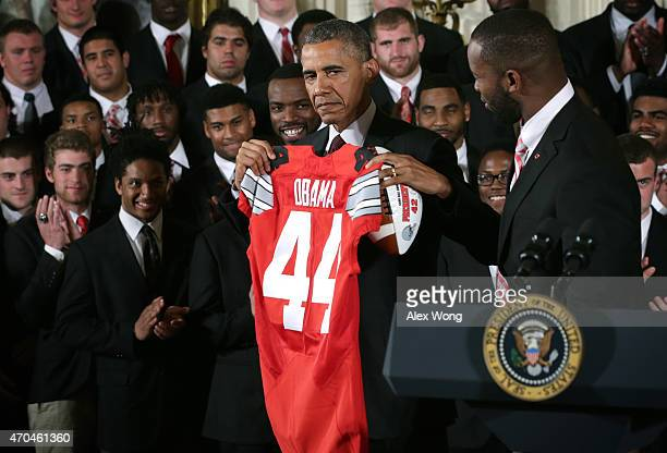S President Barack Obama receives a team jersey as he hosts the Ohio State University Buckyes football team during an East Room event at the White...
