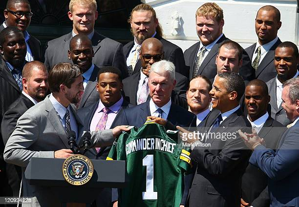 S President Barack Obama recieves a jersey from quarterback Aaron Rodgers of the Green Bay Packers during a reception for the National Football...