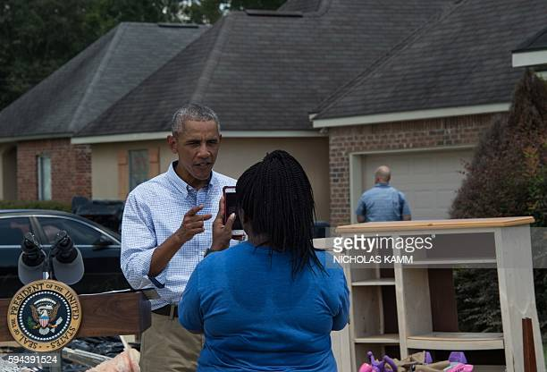 President Barack Obama records a cellphone video for a relative of resident Melissa Williams as he tours a flood-affected area in Baton Rouge,...