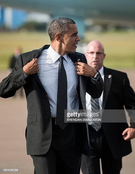 US President Barack Obama removes his jacket after arriving at Tampa International Airport on September 20 2012 in Tampa Florida Obama is traveling...