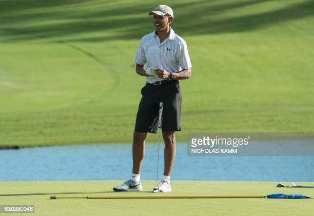 President Barack Obama retrieves his ball after putting on the 18th green at the Kapolei Golf Club in Kapolei on December 21 2016 during his annual...