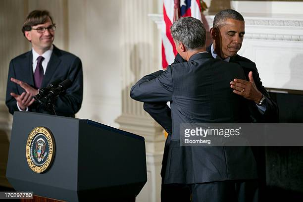 US President Barack Obama right embraces Alan Krueger chairman of the Council of Economic Advisers during a nomination announcement with Jason Furman...