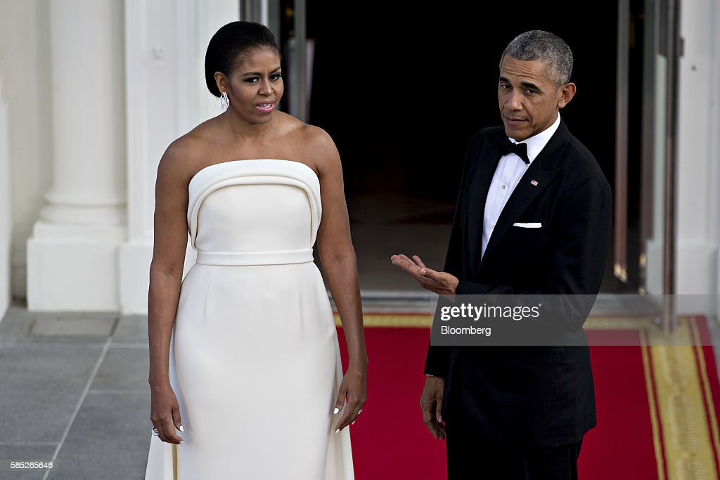 U.S. President Barack Obama, right, gestures towards U.S. First Lady Michelle Obama during an arrival for Singapore Prime Minister Lee Hsien Loong, not pictured, to the State Dinner on the North Portico of the White House in Washington, D.C., U.S., on Tuesday, Aug. 2, 2016. The occasion marks first official visit by a Singapore prime minister since 1985. Photographer: Andrew Harrer/Bloomberg via Getty Images