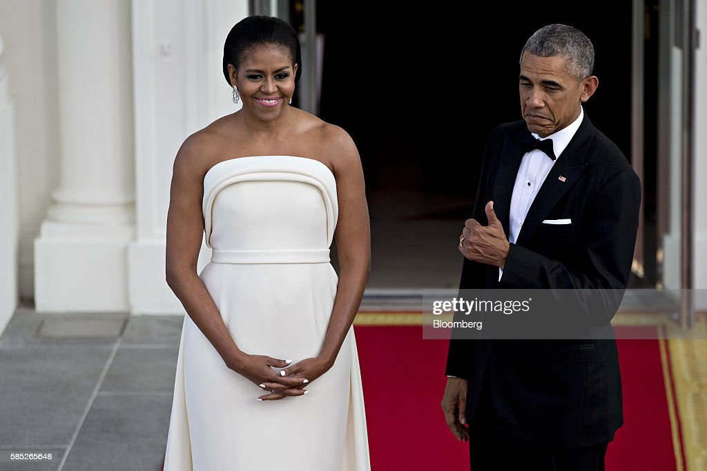 U.S. President Barack Obama, right, gestures with U.S. First Lady Michelle Obama during an arrival for Singapore Prime Minister Lee Hsien Loong, not pictured, to the State Dinner on the North Portico of the White House in Washington, D.C., U.S., on Tuesday, Aug. 2, 2016. The occasion marks first official visit by a Singapore prime minister since 1985. Photographer: Andrew Harrer/Bloomberg via Getty Images