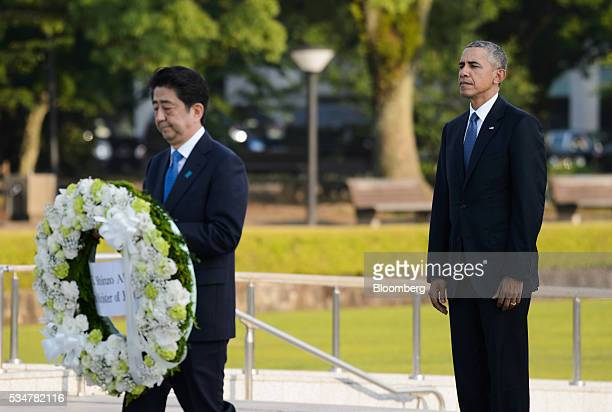 US President Barack Obama right stands as Shinzo Abe Japan's primer minister carries a wreath in front of the cenotaph at Hiroshima Peace Memorial...
