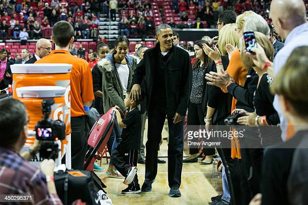 President Barack Obama rubs a boy's head as he arrives at a men's NCCA basketball game between University of Maryland and Oregon State University,...