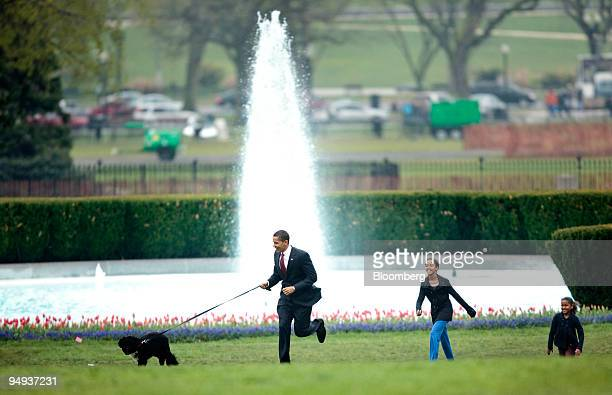 S President Barack Obama runs with the first family's new dog Bo while his daughters Malia center and Sasha right watch on the South Lawn of the...