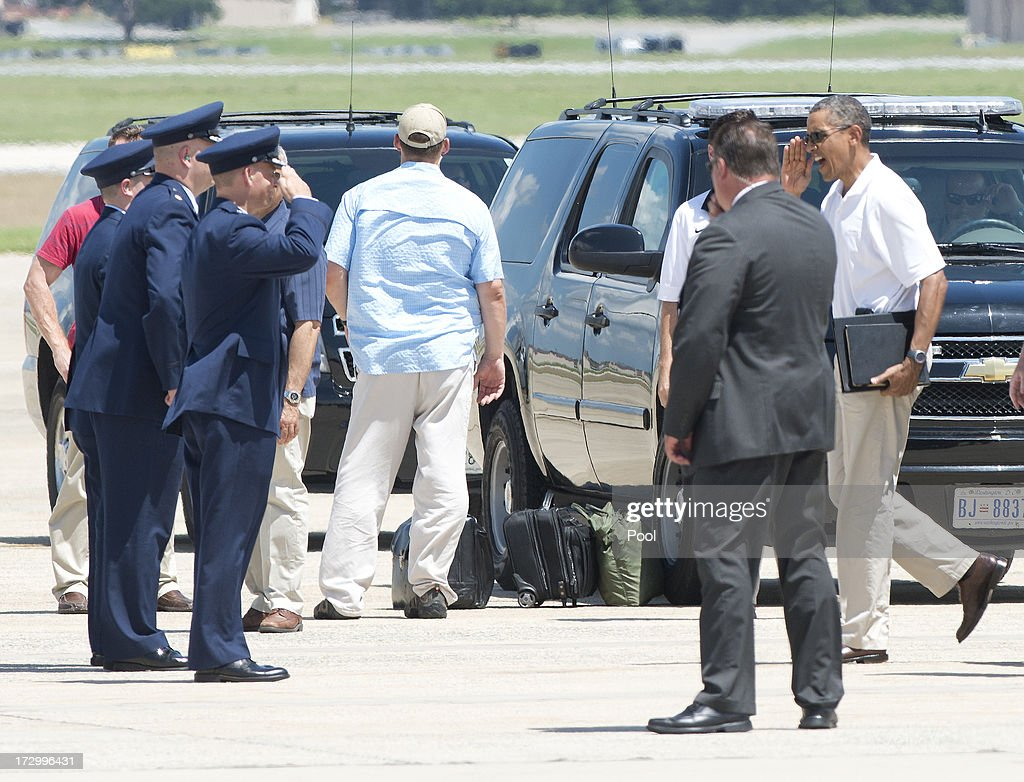 U.S. President Barack Obama salutes a group of U.S. Air Force officers as he prepares to board Marine 1 to depart Joint Base Andrews enroute to Camp David on July 5, 2013 near Camp Springs, Maryland. Obama is heading to Camp David following a round of golf.