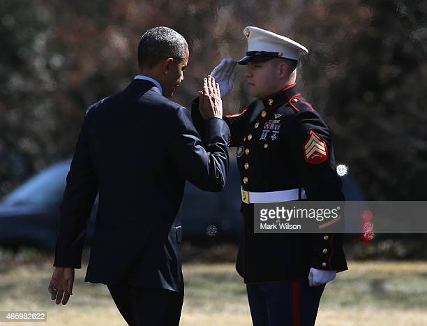 S President Barack Obama salutes a US Marine as he boards Marine One beofre departing the White House March 12 2015 in Washington DC President Obama...