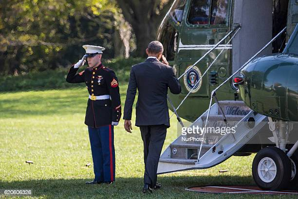 US President Barack Obama salutes a US Marine as he boards Marine One while departing from the White House November 2 2016 in Washington DC President...