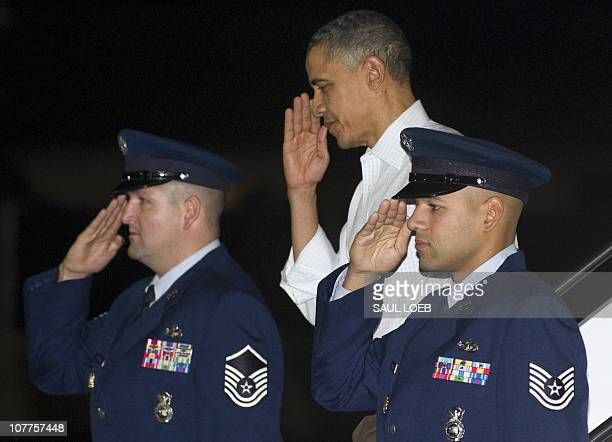 US President Barack Obama salutes as he disembarks after arriving on Air Force One at Hickam Air Force Base in Honolulu Hawaii late on December 22...