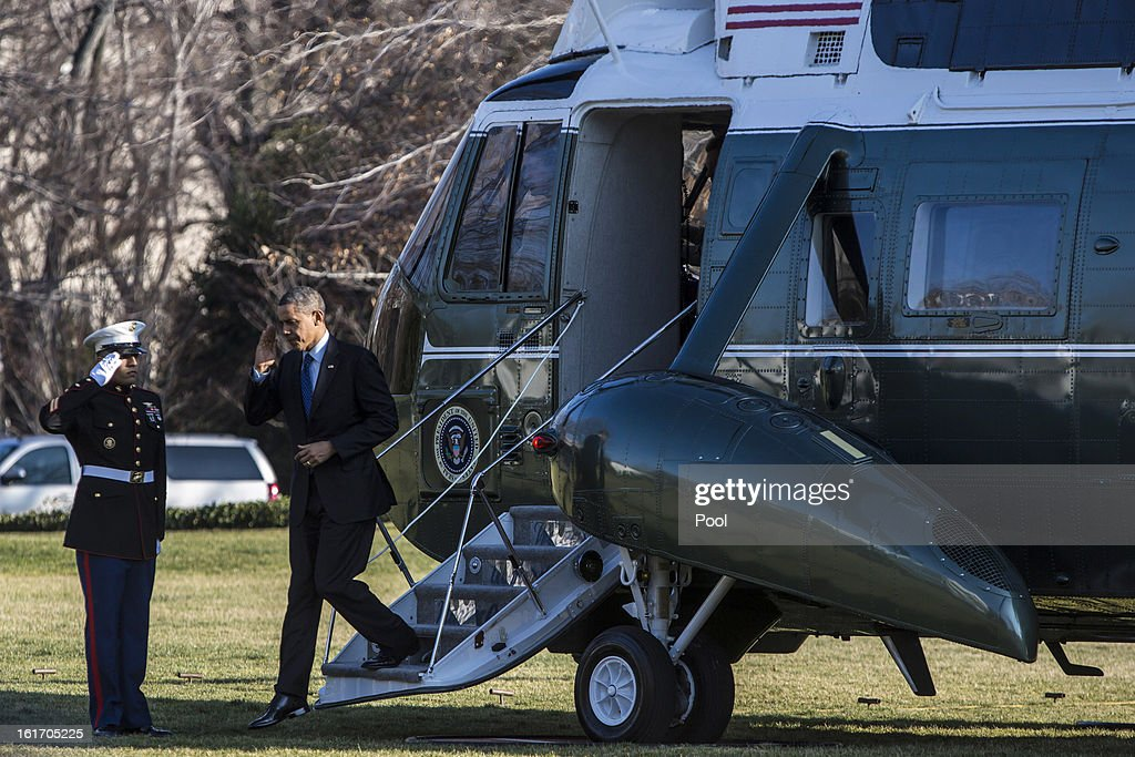 U.S. President Barack Obama salutes as he walks off Marine One after arriving at the White House February 14, 2013 in Washington, DC. Obama was returning after a trip to Decatur, Georgia to tout his pre-school initiative.