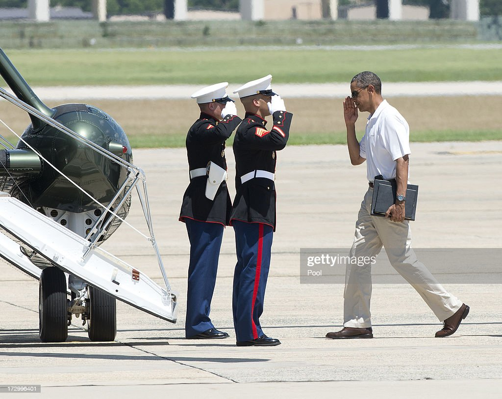 U.S. President Barack Obama salutes the U.S. Marine Guards as he prepares to board Marine 1 to depart Joint Base Andrews enroute to Camp David on July 5, 2013 near Camp Springs, Maryland. Obama is heading to Camp David following a round of golf.