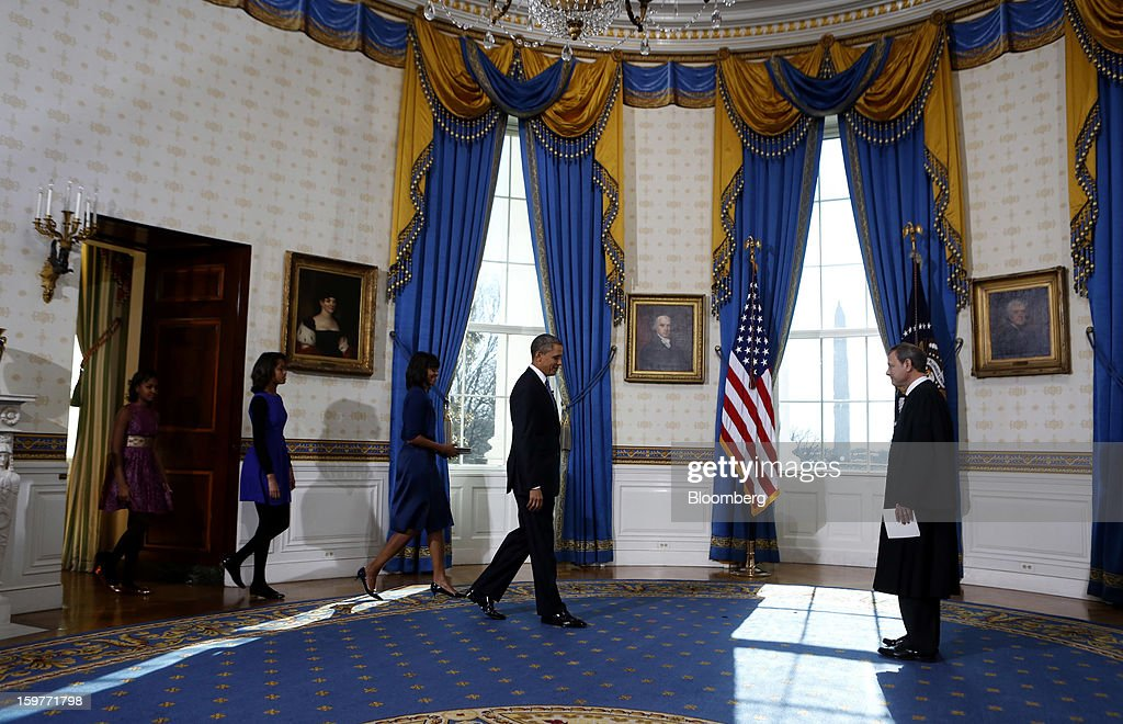 U.S. President Barack Obama, second from right, enters the Blue Room to take the oath of office from U.S. Supreme Court Chief Justice John Roberts, right, followed by daughters Sasha Obama, left, Malia Obama, second from left, and first lady Michelle Obama at the White House in Washington, D.C., U.S., on Sunday, Jan. 20, 2013. As he enters his second term Obama has shed the aura of a hopeful consensus builder determined to break partisan gridlock and adopted a more confrontational stance with Republicans. Photographer: Larry Downing/Pool via Bloomberg