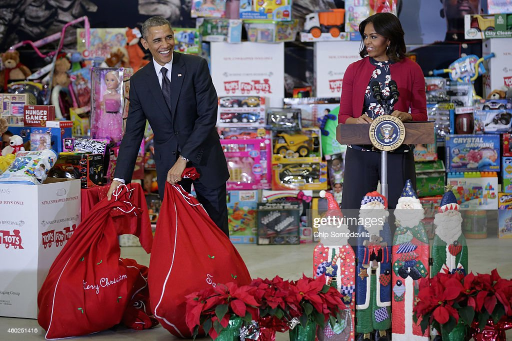 US President Barack Obama (L) sets down bags of toys as he and first lady Michelle Obama deliver gifts donated by Executive Office of the President staff to the Marine Corps Reserve Toys for Tots Program at Joint Base Anacostia-Bolling December 10, 2014 in Washington, DC. For 67 years the Toys for Tots program has worked with local communities to collect and distribute toys and gifts for less fortunate children throughout the United States.