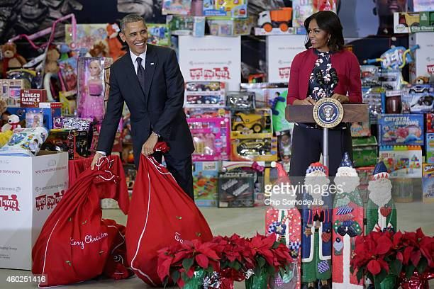 President Barack Obama sets down bags of toys as he and first lady Michelle Obama deliver gifts donated by Executive Office of the President staff to...
